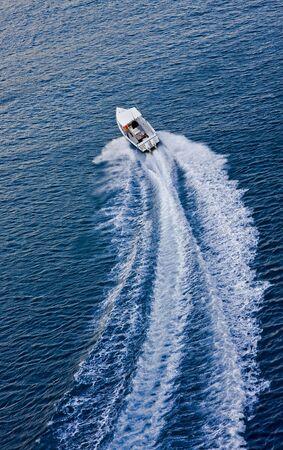 A white motorboat speeding away across a blue bay Stock Photo - 4678689
