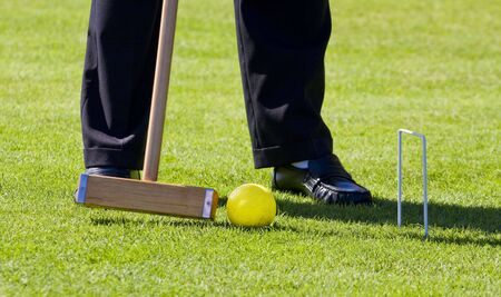 A player making a croquet shot putting a yellow ball through a wicket Фото со стока