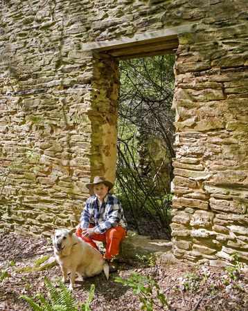 dog rock: A nice looking hispanic man outside by an old rock wall with dog