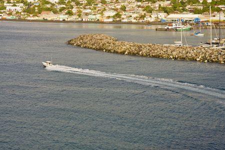 A fishing boat off the coast past a sea wall Stock Photo - 4756010