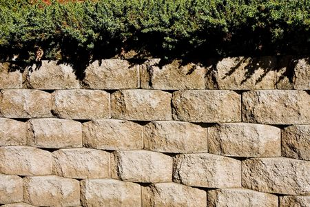 A concrete block retaining wall topped with hedge