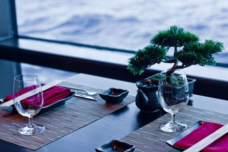 A formal place setting in an Asian restaurant featuring bonsai trees and chopsticks