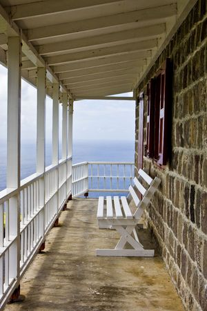 An empty white bench on a walkway outside an old block stone coastal building Stock Photo - 4880382