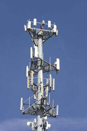 A cellular telephone tower against a blue sky
