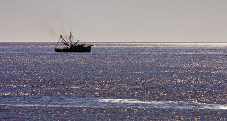shrimp boat: A shrimp boat off the coast in the morning