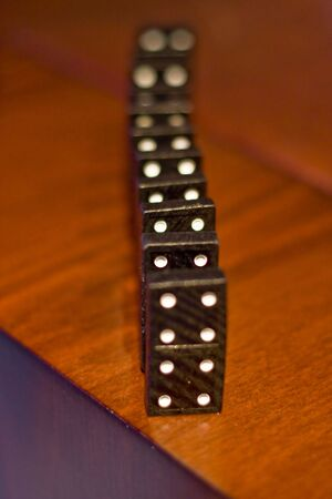 Dominoes lined up on a wood table Stock Photo