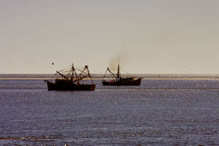 Two Shrimp Boats off the coast in the morning photo