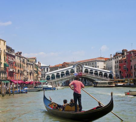 A gondola in the Grand Canal in Venice with the Rialto Bridge in the background