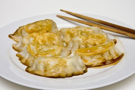potstickers: A plate of asian potstickers and chopsticks ready to eat Stock Photo
