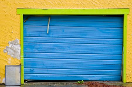 A blue loading door on an old yellow building