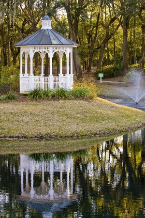 A white gazebo next to a lake