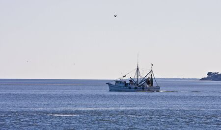 shrimp boat: A shrimp boat heading out into the bay in the morning
