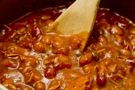 stirring: Stirring a pot of hot chili with a wooden spoon