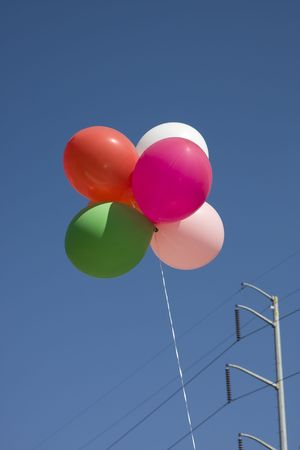 high powered: Colorful balloons rising into the blue sky by a high powered electric line