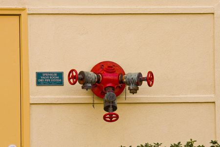 A red fire sprinkler valve on a commercial building photo