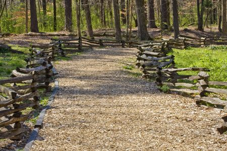 A natural trail in a forest park made of wood chips and a split rail fence photo