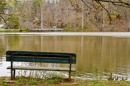 An old empty green bench on the shore of a lake in winter photo