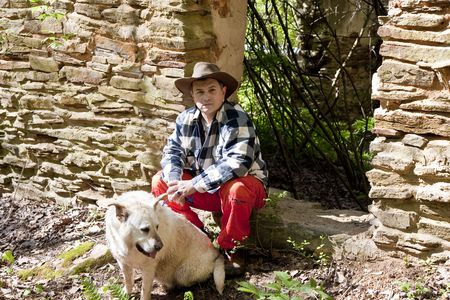Hispanic Man in plaid shirt and orange pants with a dog by an old rock wall Stock Photo