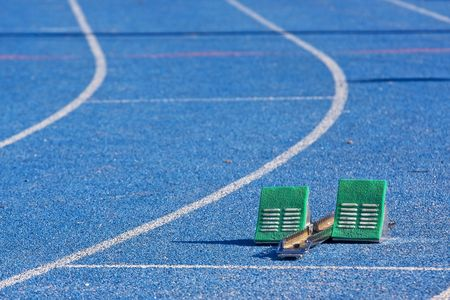 Green starting blocks in a lane of a blue track photo