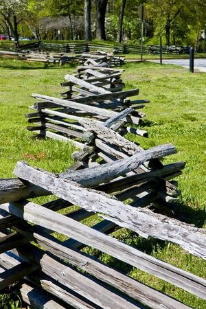 A split rail fence disappearing into the distance by a green field photo