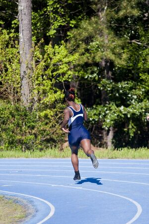 A young woman entering the curve on a track during a race