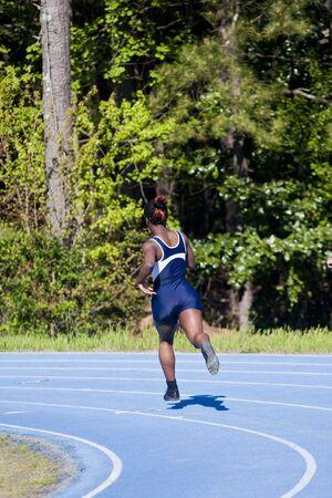 Een jonge vrouw in de curve op een track tijdens een race Stockfoto