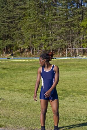 A track runner in blue warming up or cooling down at a track meet Archivio Fotografico