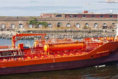 A new tanker painted bright orange in a port in florence, italy
