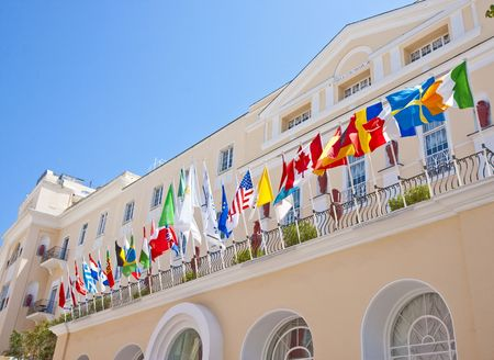 A beautiful hotel in Capri overlooking the sea with an array of flags over the front entrance Stock Photo