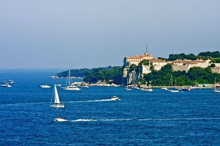 An old French fortress on an island off the coast of Cannes iwth pleasure boats in the blue water of the Mediterranean Stock Photo