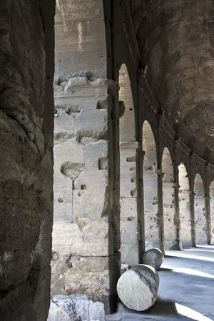 A row of columns and arches under the ancient Roman Coliseum