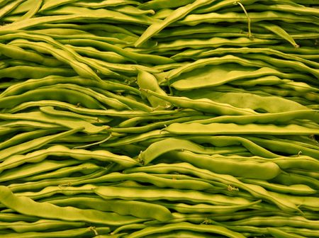 A bin of fresh green beans in a vegetable market