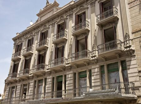 An old classic European apartment building with shutters and iron balconies