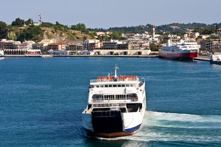 A large ferry on the coast of greece in a blue bay