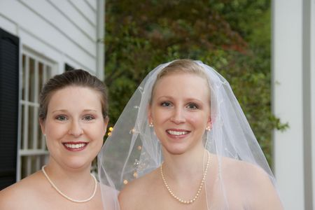 The bride and the maid of honor smiling photo