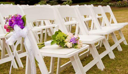 꽃과 야외 결혼식에서 흰색 접는 의자
