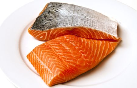 eating fish: Fresh salmon fillets with skin on a white plate