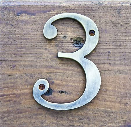 three: Brass Number three on a wood plaque Stock Photo