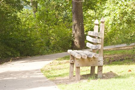 An old rustic wooden bench on a paved walking trail in the park