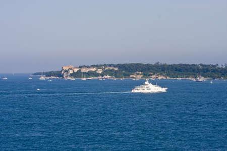A white luxury yacht cruising across a calm blue bay