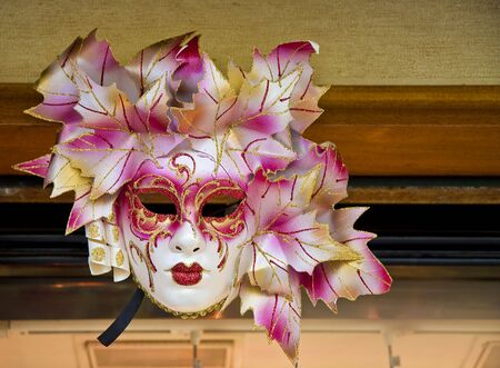 A colorful Venetian mask on the wall of a shop Stok Fotoğraf