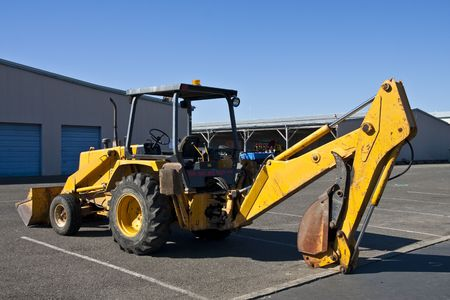 heavy industry: A large yellow heavy earth moving equipment in a parking lot under a blue sky Stock Photo