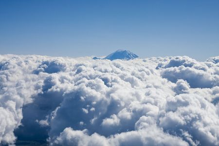 Clouds to the horizon and a mountain against a blue sky