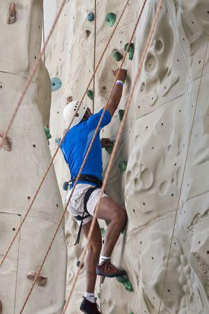 로프 하네스로 바위 벽을 등반하는 남자