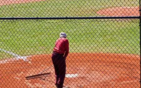 groundskeeper: A man raking dirt around home plate on a baseball field Stock Photo