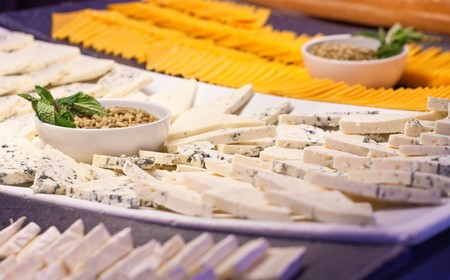 A selection of sliced cheeses on a salad bar Stok Fotoğraf