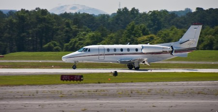 A large private jet landing on a regional runway Stock Photo