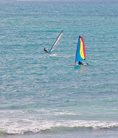 windsurfers: Two windsurfers riding the surf in the blue ocean