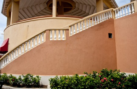 curving: A curving staircase around a peach colored stucco building