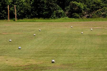 Un campo de f�tbol con muchas bolas dispersos alrededor  Foto de archivo - 7507912